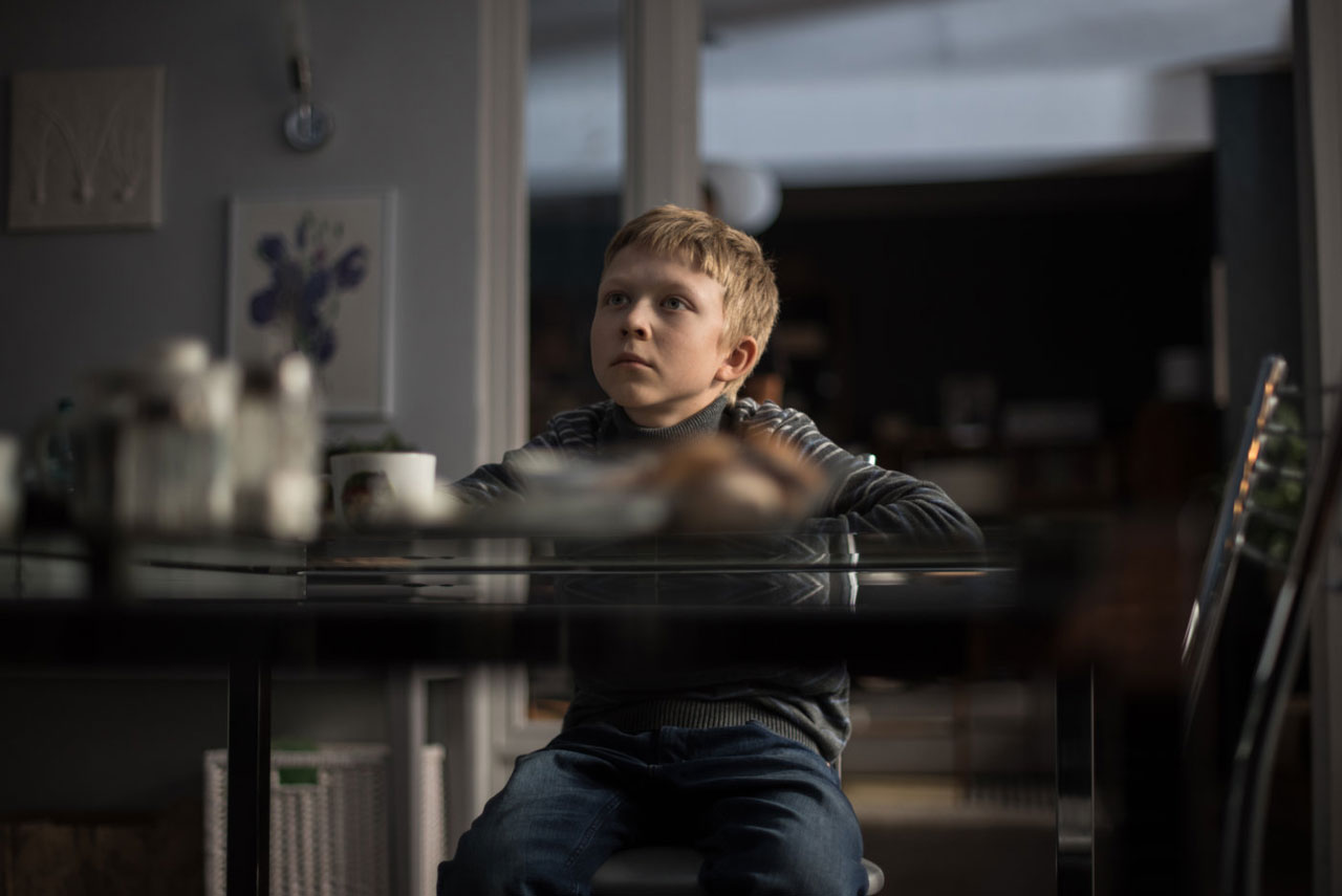 """Szene aus """"Loveless"""". Kind sitzt am Tisch"""