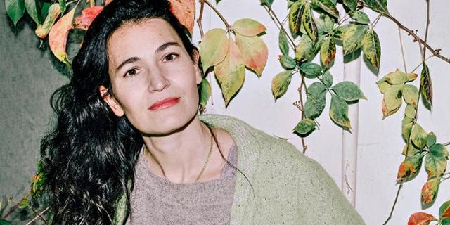 Nicole Krauss mit langen schwarzen Haaren steht unter den halb welken Blättern einer Kletterpflanze.