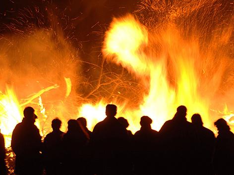 Menschen stehen vor einem großen Osterfeuer
