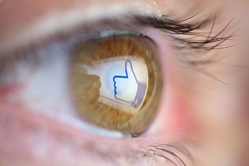 Im Auge spiegelt sich ein Facebook-Daumen
