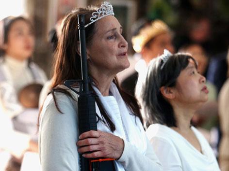 Eine Frau hält ein Sturmgewehr während eines Gottesdienstes für Waffen
