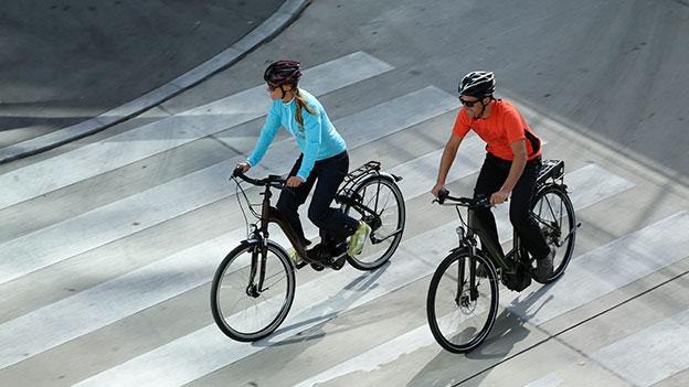 Paar fährt e-Bikes.