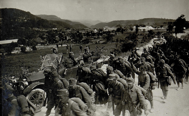 Kaiser Karl im Auto neben marschierenden Soldaten