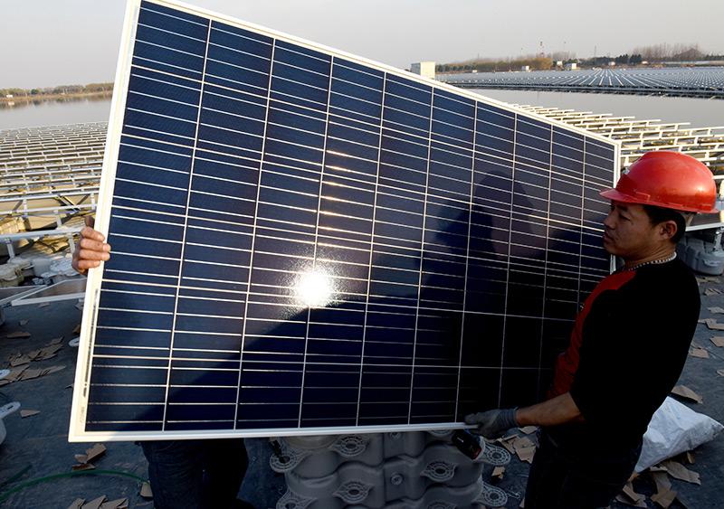 Chinesischer Arbeiter montiert ein Solarpanel