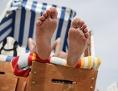 eine Urlauberin sonnt sich im Strandkorb