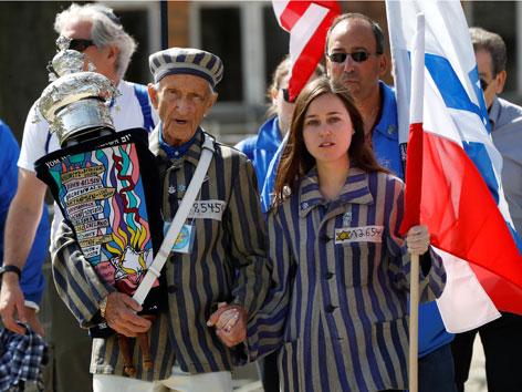 Ein Holocaust-Überlebender Hand in Hand mit einer jungen Jüdin beim Marsch der Lebenden in Auschwitz. Beide in Stäflingsgewand.