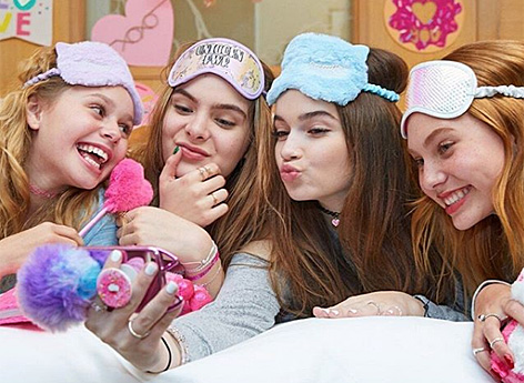 Vier Mädchen mit bunten Plüsch-Schlafmasken am Kopf machen ein Selfie