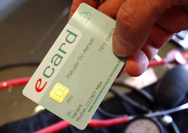 Ein Arzt hält das Muster einer E-Card.
