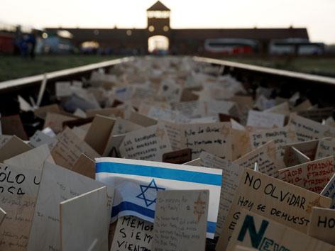 """Tausende Karten von Teilnehmern am """"Marsch des Lebens"""" zwischen den Schienen vor der Einfahrt nach Auschwitz."""