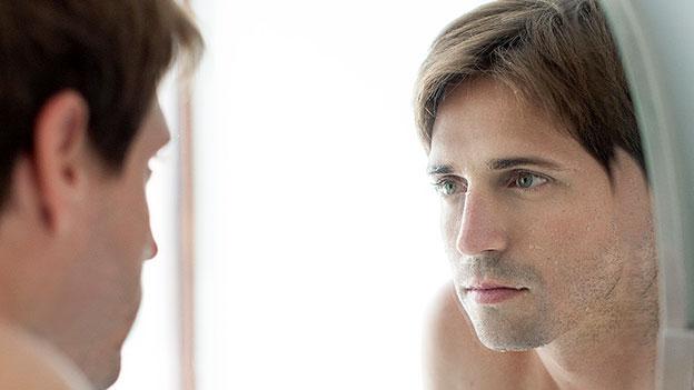 Mann schaut in den Spiegel