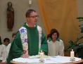 Pfarrer mit freundlicher Geste spricht am Altar