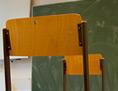 Sesseln auf Tischen in einer Schule, vorne eine Tafel