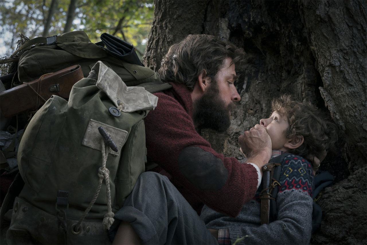 Ein Mann und ein Kind in einem Wald. Der Mann hält dem Kind den Mund zu.