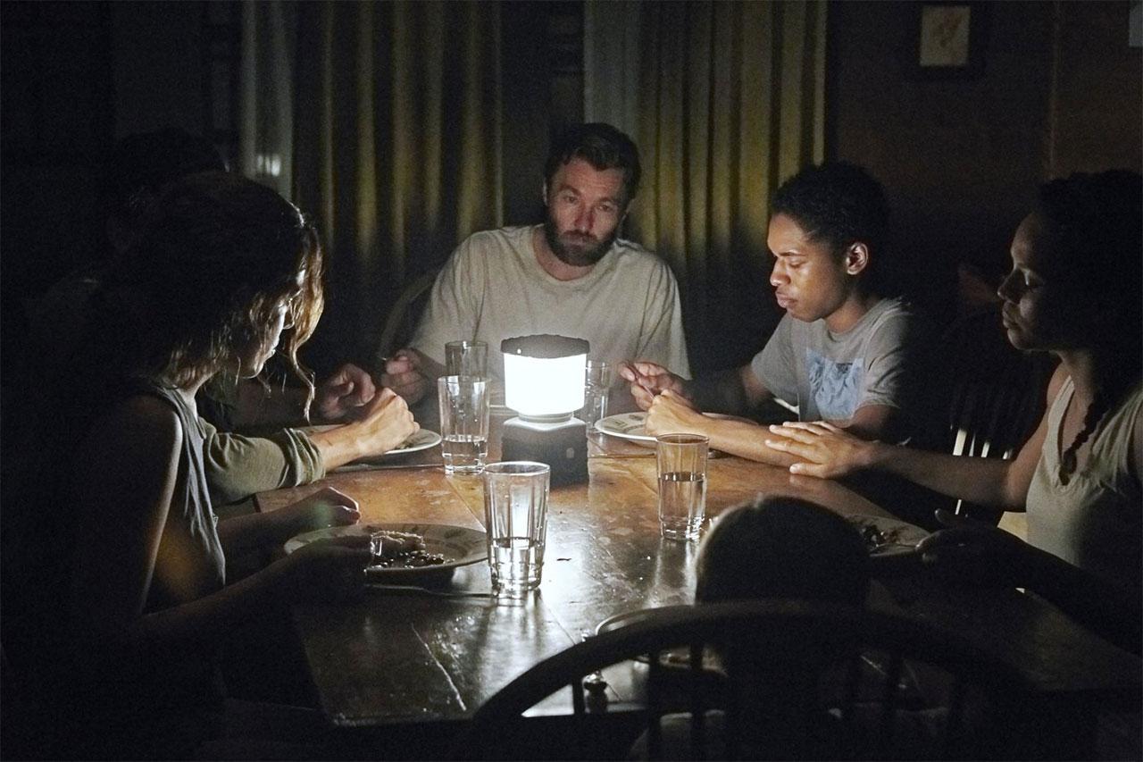 Eine Gruppe von Menschen beim Essen an einem Tisch. Es brennt nur eine kleine Lampe.