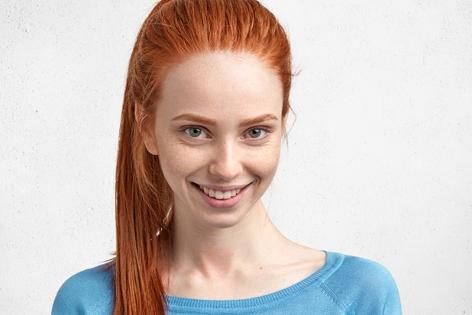 Eine rothaarige Frau lächelt in die Kamera