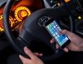 Ein Mann sitzt in einem Auto am Steuer und hält ein Smartphone in der Hand
