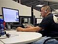 Ein Mann mit Headset telefoniert vor dem Computer