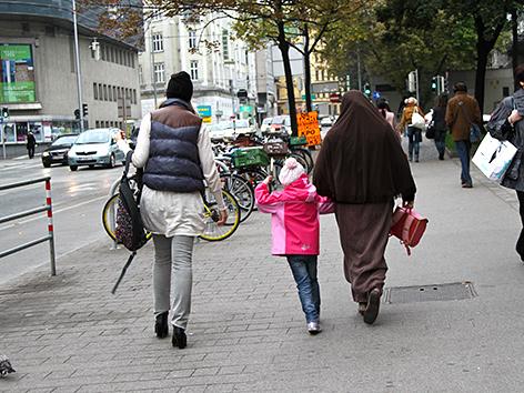 Zwei Frauen und ein Kind auf der Straße, eine Frau ist verschleiert