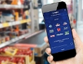 Eine Hand hält ein Smartphone mit geöffneter Payback-App, im Hintergrund Supermarkt-Regale
