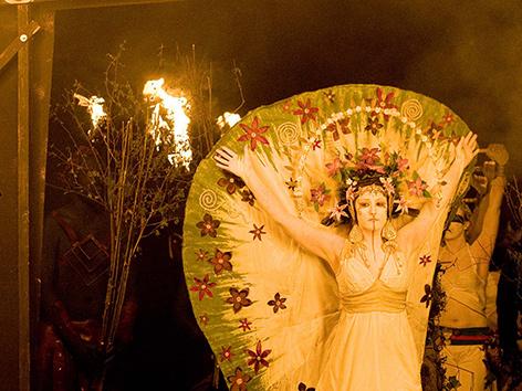 Eine Frau in Fantasiegewand mit erhobenen Armen bei einer Performance   bei einem Beltane-Fest