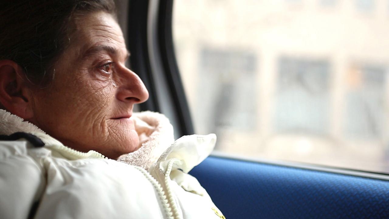Eine ältere Frau sitzt in einem Auto, eine Träne läuft ihr über das Gesicht