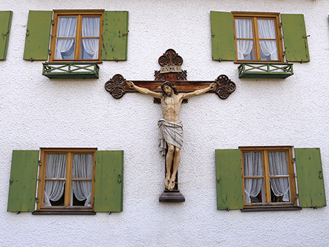 An einem Bauernhaus in Bayern hängt ein Kruzifix