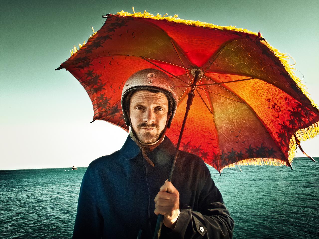 DJ Koze mit Sonnenschirm am Meer