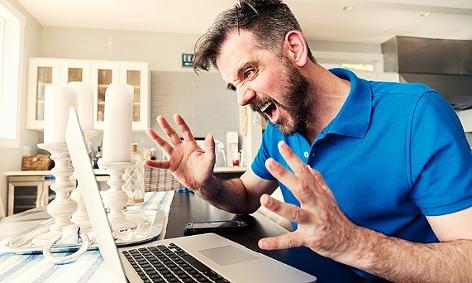 Mann ärgert sich beim Laptop sitzend