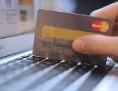 Ein Mann zückt seine Kreditkarte zum Einkaufen im Internet