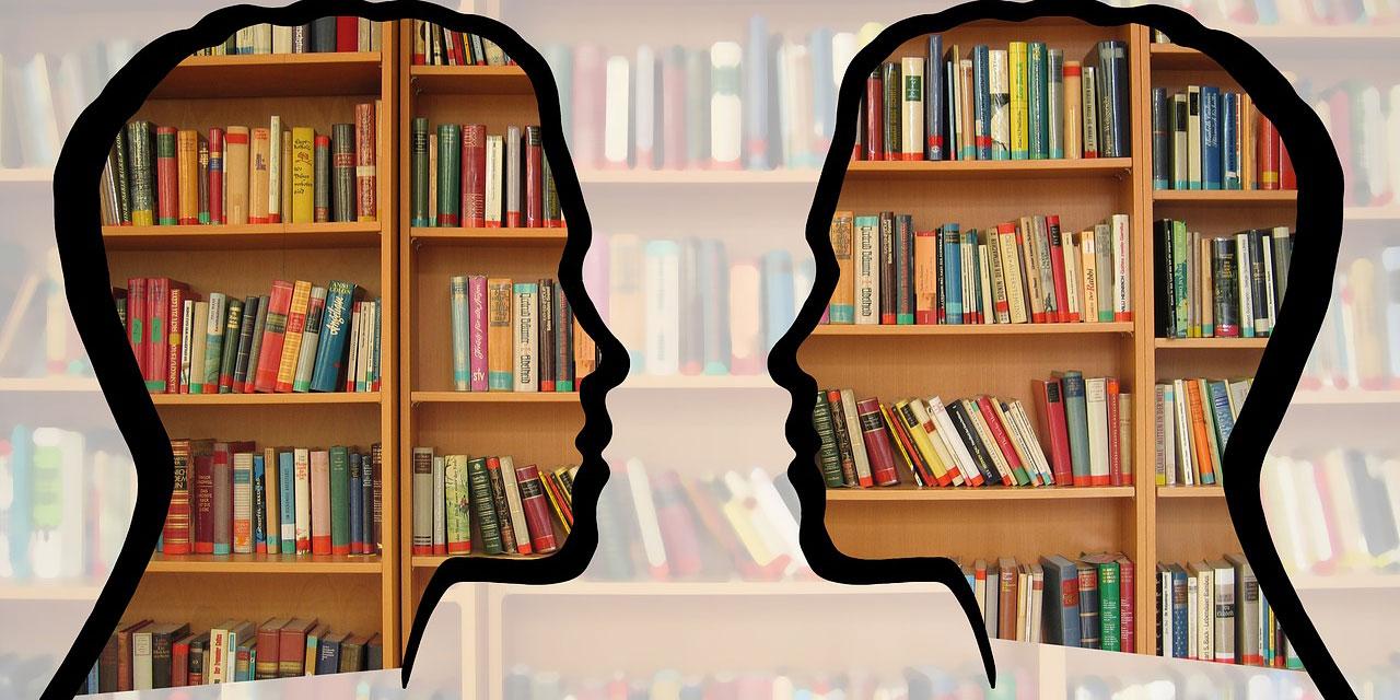 Silhoutten zweier Köpfe vor einem Bücherregal