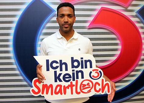 """Cesar Sampson mit """"Ich bin kein Smartloch""""-Schild"""