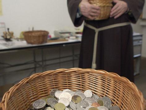 Ein Ordensmann steht hinter einem Korb mit Münzen
