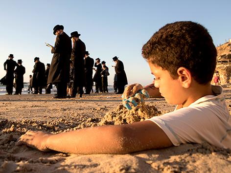 Ein Kind spielt im Sand an einem Strand in Herzliya, Israel, im Hintergrund betende Ultraothodoxe