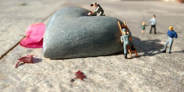 Kleine Miniaturmenschen bearbeiten ein Steinherz