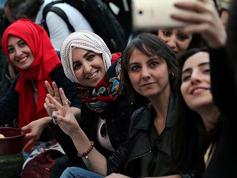 Vier Frauen machen ein Selfie vor dem Fastenbrechen im Ramadan. Zwei tragen kopftücher, zwei nicht.