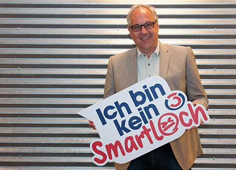 """Gerry Foitik lacht und hält ein """"Ich bin kein Smartloch""""-Schild in der Hand"""