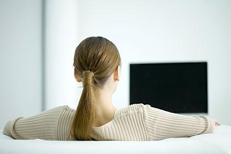 Frau sitzt vor TV-Gerät