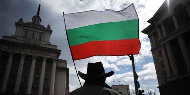 Mann mit bulgarischer Fahne vor dem Sitz der Regierung