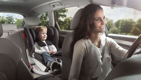 Frau fährt Auto mit Kind in Kindersitz