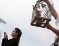 Eine Frau in Kambodscha betet zu Vesakh, eine andere lässt Vögel aus einem Käfig frei.