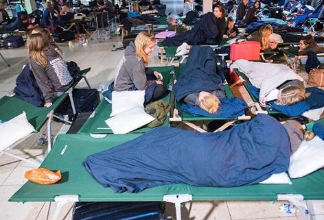 Reisende Abiturienten ruhen sich am Flughafen Hamburg auf Feldbetten aus.