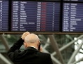 : Ein Mann steht telefonierend vor der Anzeigetafel im Flughafen Hamburg und fasst sich an den Kopf.