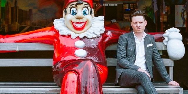 Konstantin Gropper sitzt nemebn einem Clown im Wiener Prater