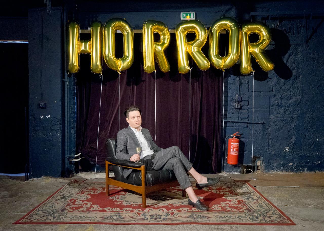 """Konstantin Gropper von get Well Soon sitzt unter dem Schriftzug """"Horror"""" aus goldenen Luftballonbuchstaben"""