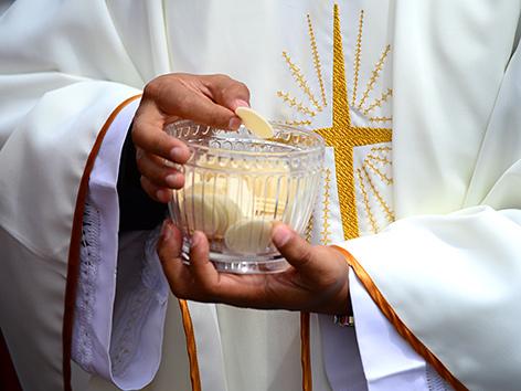 Ein Priester verteilt die Kommunion