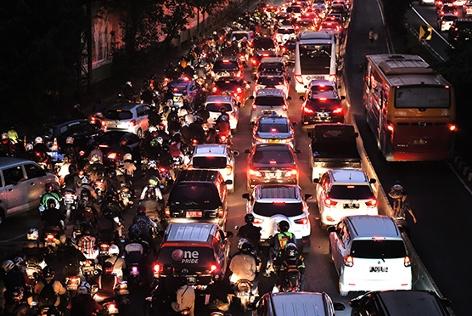 Abendlicher Verkehrsstau mit Autos und Motorrädern