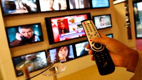Eine Fernbedienung vor mehreren Fernsehern