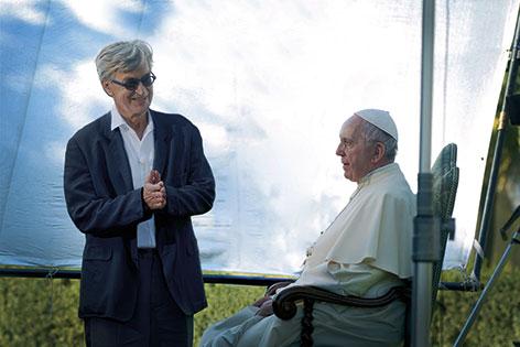 Wim Wenders steht vor dem sitzenden Papst Franziskus