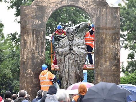 Eine Bronzestatue Papst Johannes Pauls II. in der bretonischen Stadt Ploemel wird von Arbeitern zugedeckt und verschoben