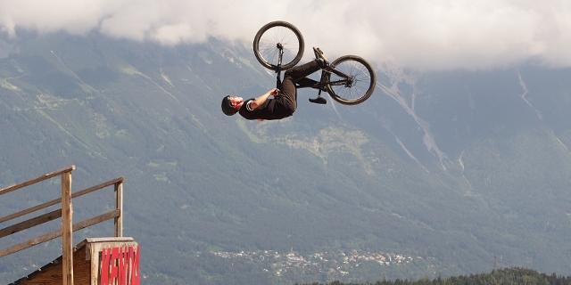 Mountainbiker backflippt von einer Holzrampe